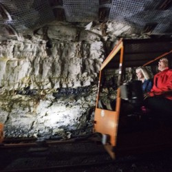 In this Oct. 18, 2014 photo, tourists ride a rail car in the Portal 31 coal mine that has been turned into a tourist attraction in Lynch, Ky.