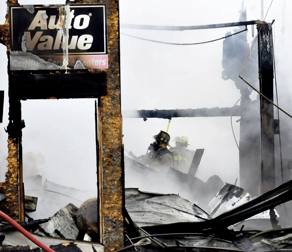 Two firefighters emerge from the smoky ruins of Ray's Auto garage in North Belgrade destroyed by fire on Monday.