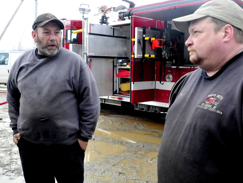 Ray Frappier, left, owner of Ray's Garage business and property owner Percy French speak as firefighters extinguish the fire that destroyed the North Belgrade business on Monday.