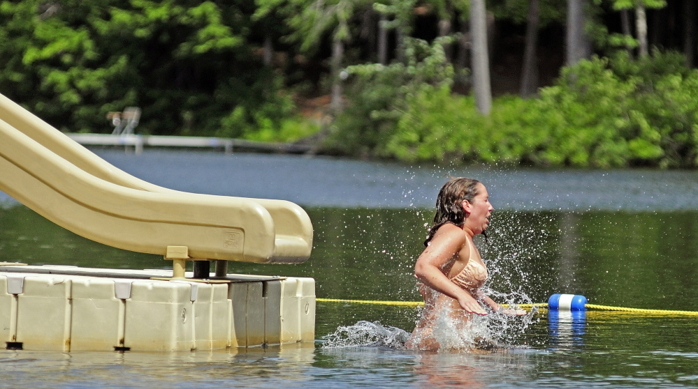 Kristin Lamontagne hits the water of Three Cornered Pond after coming off the slide at Bicentennial Nature Park in Augusta last summer. The city park is currently open to Augusta residents only, but there is a proposal to open the park to non-residents as well.