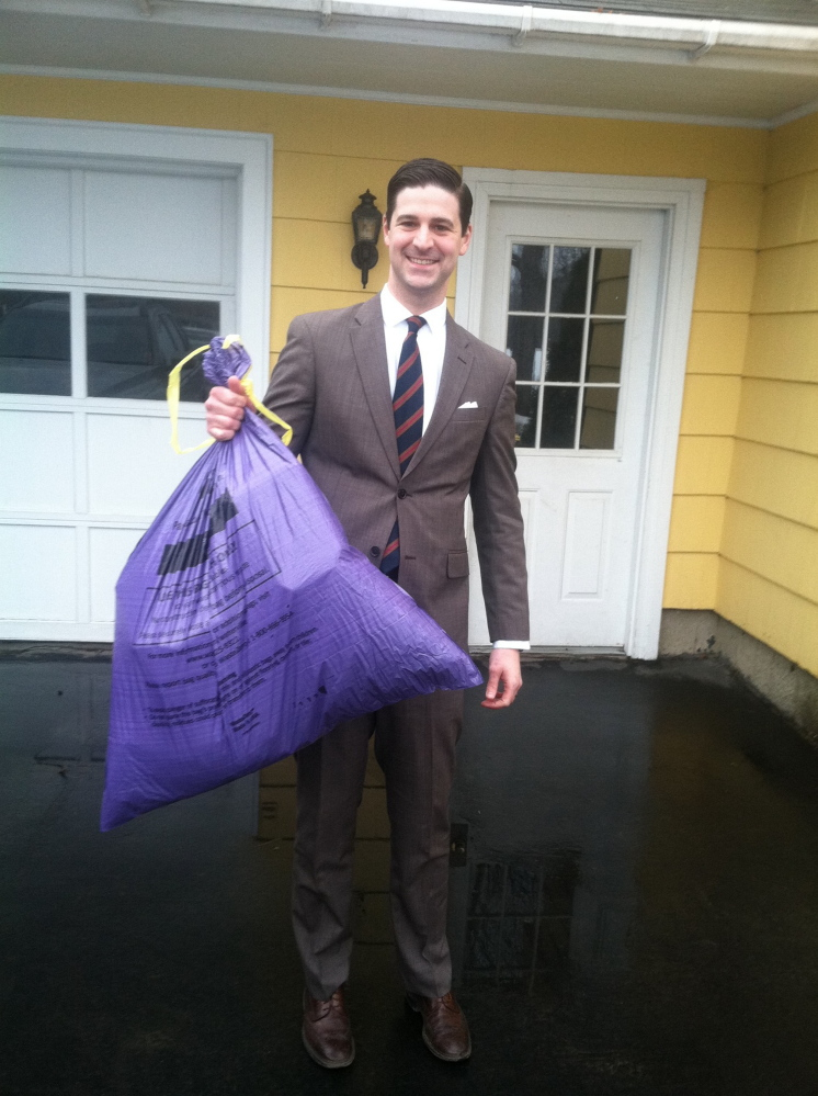 Waterville Mayor Nick Isgro, holding his city trash bag Monday, has scheduled an open community meeting next month to discuss issues relating to the city's pay-as-you-throw trash collection program. A referendum on whether to continue the program will be held in June.