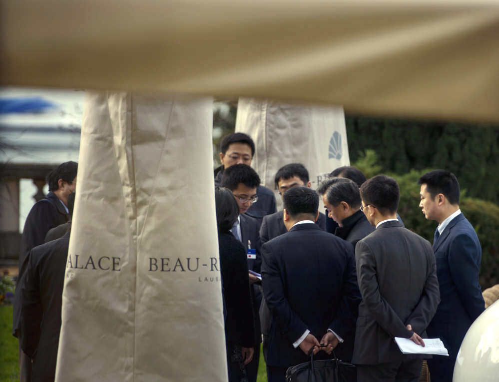 Chinese Foreign Minister Wang Yi, third from right, speaks with members of the Chinese delegation at the Beau Rivage Palace Hotel, on Tuesday in Lausanne, Switzerland.
