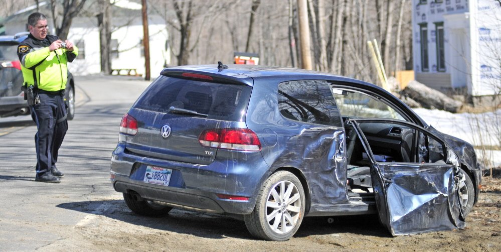 Winthrop police officer Paul Ferland photographs a wrecked car on Tuesday after it was involved in a collision with a utility pole on Winthrop Center Road, Route 135, near South Road in Winthrop. Driver Edwin Ward and passenger Sarah Ward were taken to Central Maine Medical Center in Lewiston after the crash.