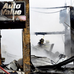 Two firefighters emerge from the smoky ruins of Ray's Auto garage in North Belgrade that was destroyed by fire on Monday.