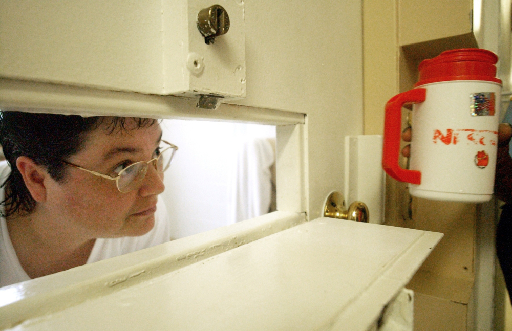 Kelly Gissendaner, the only woman on Georgia's death row, peers through the slot in her cell door as a guard brings her a cup of ice at Metro State Prison in Atlanta.
