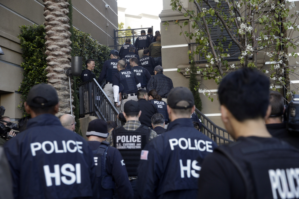 Federal agents enter an upscale apartment complex Tuesday in Irvine, Calif., where authorities say a birth tourism business charged pregnant women $50,000 for lodging, food and transportation. The key draw for travelers is that the United States offers birthright citizenship.