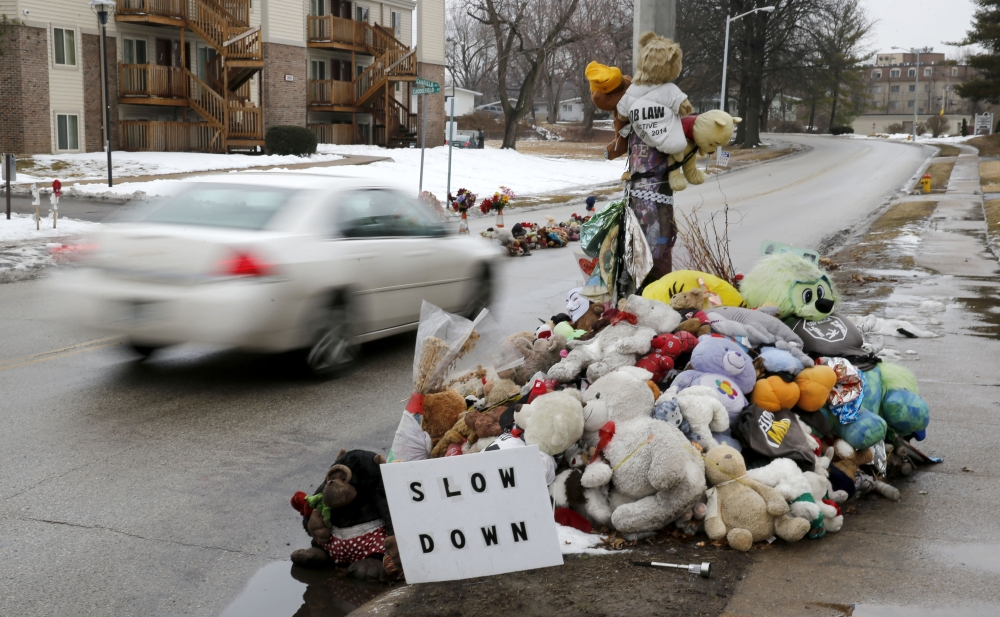 A car passes a memorial for Michael Brown, who was shot and killed by Ferguson, Mo., Police Officer Darren Wilson last summer, Tuesday, in Ferguson.