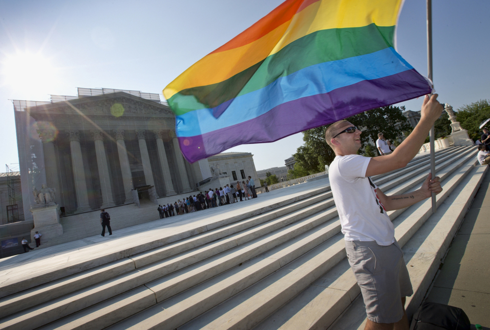 Vin Testa of Washington waves a rainbow flag in support of gay rights outside the Supreme Court in Washington in June 2013.