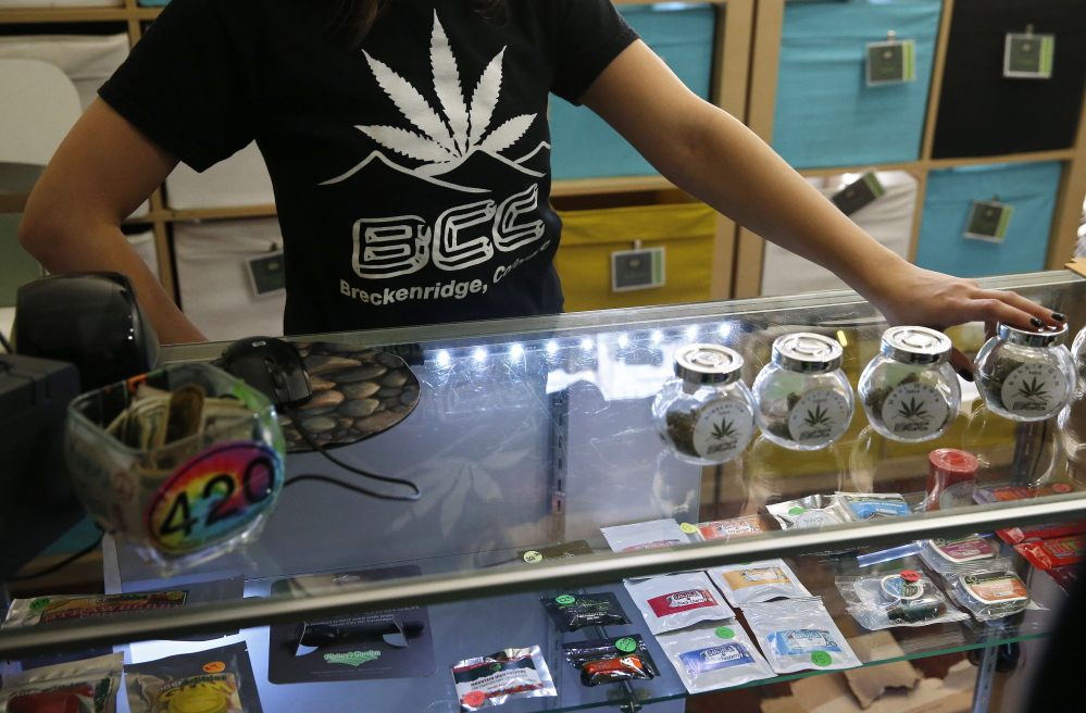 A pot store employee talks with customers inside the Breckenridge Cannabis Club, which sells recreational marijuana products, in the ski town of Breckenridge, Colo., in December.
