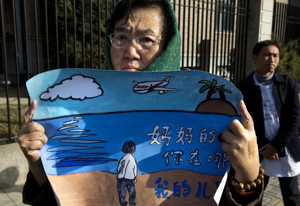 """A woman whose son was on board the missing Malaysia Airlines Flight 370 holds a banner reading """"Mother's heart is broken, where are you my son"""" in Beijing on Sunday."""