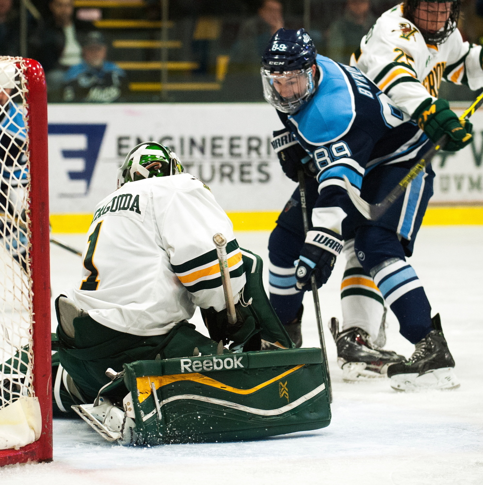 Maine's Blaine Byron looks for a rebound in front of Vermont goalie Mike Santaguida during Game 3 of a Hockey East playoff series Sunday night in Burlington, Vermont. Vermont eliminated the Black Bears with a 3-2 overtime victory.
