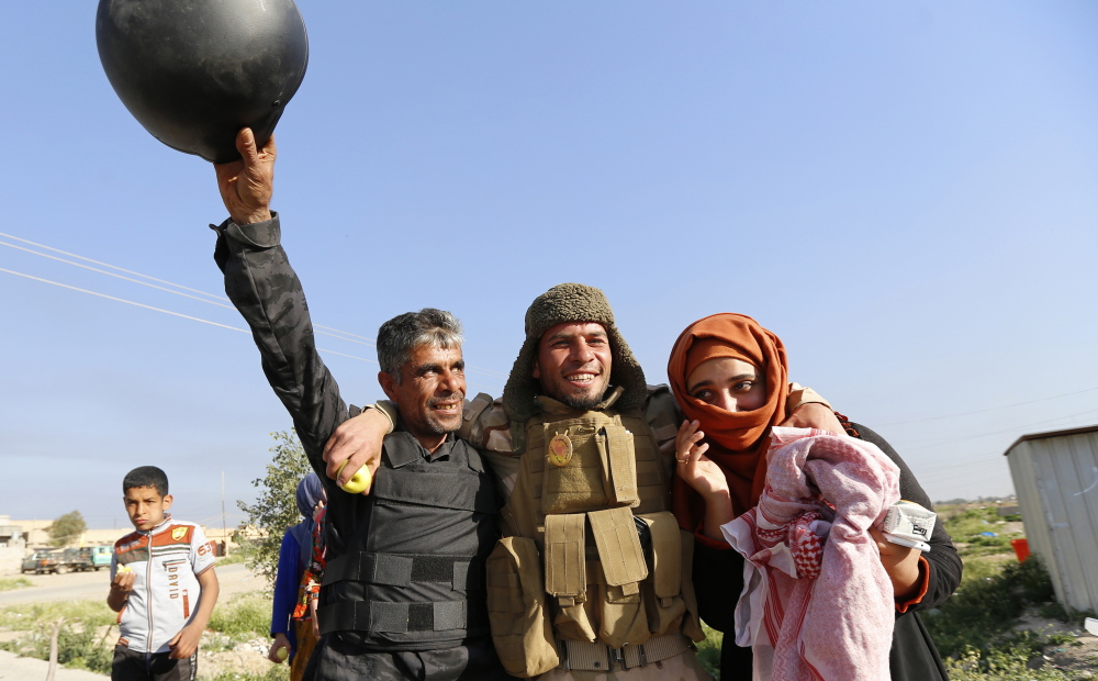 Residents welcome a relative who is part of militia in the town of al-Alam.
