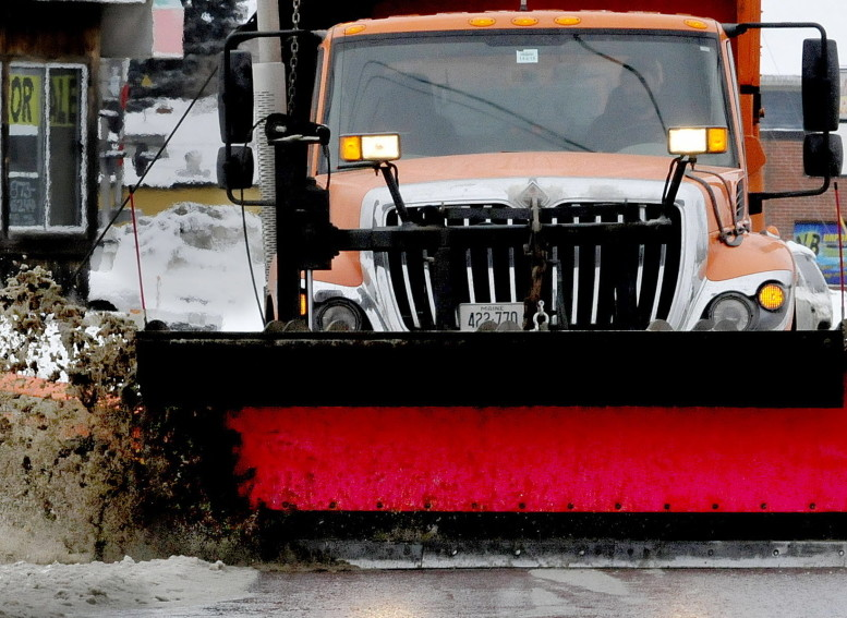 A Waterville Public Works plow truck pushes slush off streets in the city Sunday. David Leaming/Staff Photographer