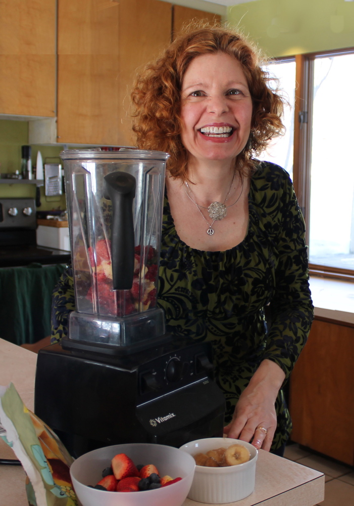 "Lisa Whited poses by the makings of a smoothie in her Portland kitchen. She went vegan in 2013 after attending a lecture called ""Power Foods for the Brain."""