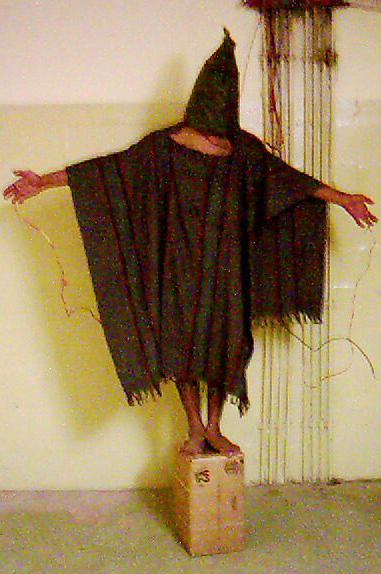 A 2003 image shows a detainee at the Abu Ghraib prison in Baghdad, Iraq, with wires attached to him.