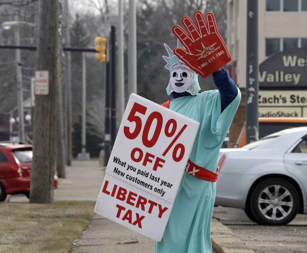 A Liberty Tax Service employee dressed as Lady Liberty waves to drivers on Saturday in Berea, Ohio. Federal regulators want tighter control of tax preparers to make sure consumers understand the fees and risks of refund advances.