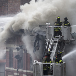 Firefighters spray water on a collapsed building in New York's East Village on Thursday after an apparent gas explosion leveled an apartment building, partially destroyed another and launched rubble and shards of glass across streets, injuring at least a dozen people.