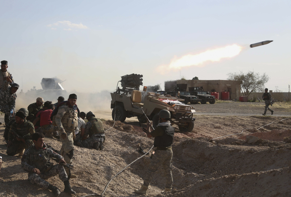 Iraqi security forces launch a rocket toward Islamic State extremist positions during clashes in Tikrit, Iraq, on Thursday. But the largely Iranian-backed forces reacted with fury after coalition planes launched 17 airstrikes on Tikrit during the first wave of attacks.