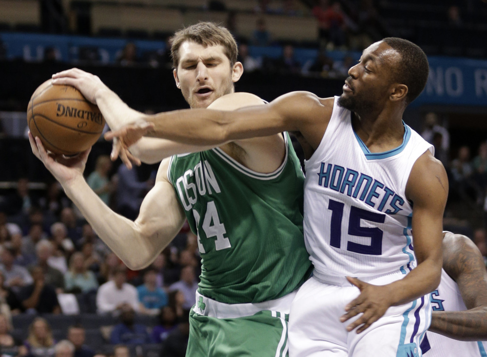 The Celtics' Tyler Zeller grabs a rebound in front of the Charlotte Hornets' Kemba Walker during the first half of Monday night's game in Charlotte, N.C.
