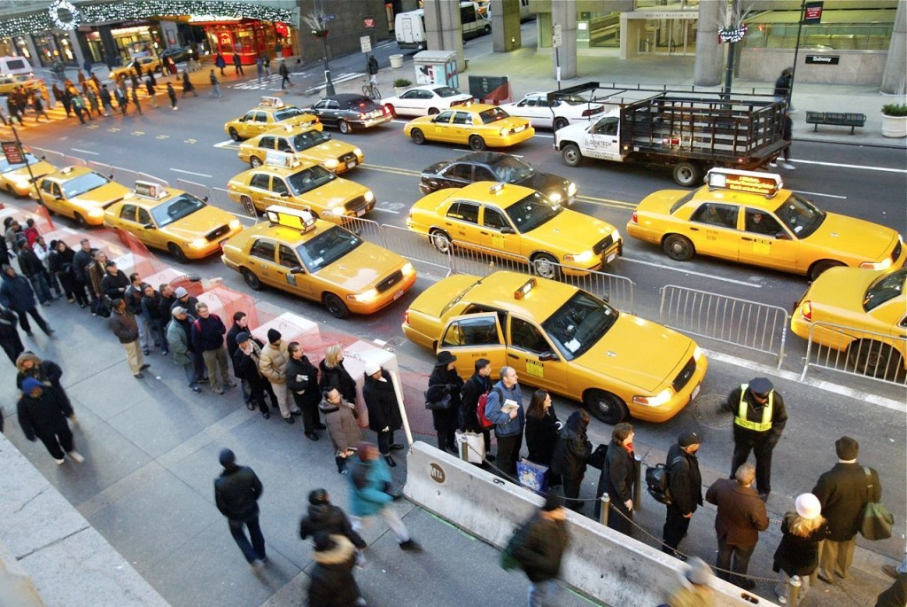 Morning rush hour commuters line up for cabs outside Grand Central Station. City residents have hailed yellow taxis with a whistle and a wave for generations. The Associated Press