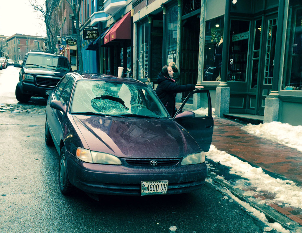 Kassie Grant removes items from her car after its windshield was shattered by falling ice Wednesday afternoon on Exchange Street. The car was later towed away.