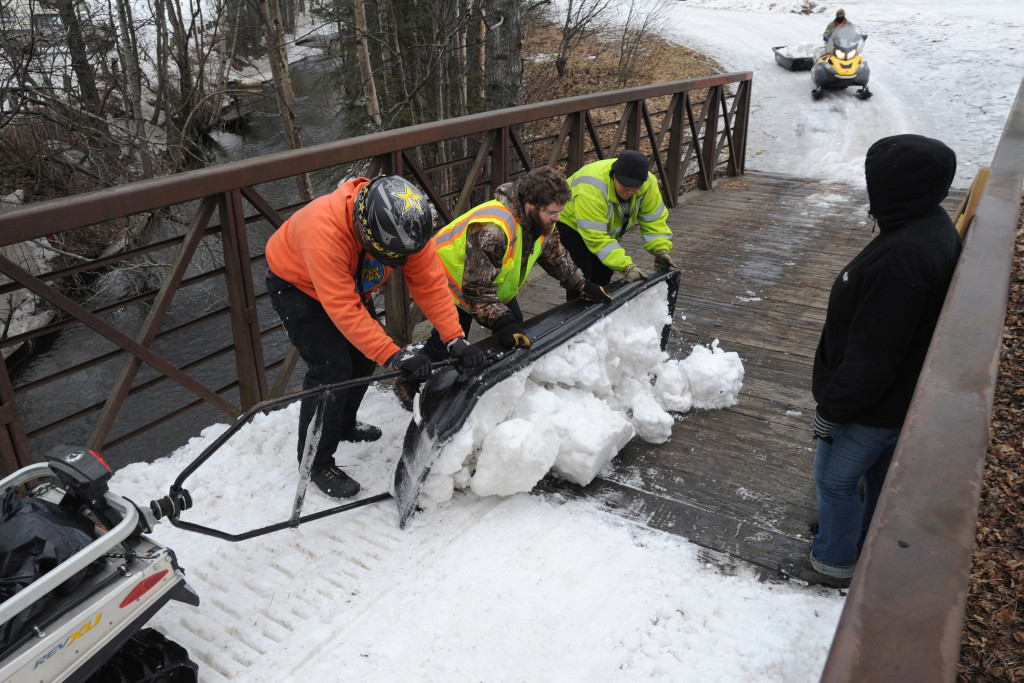 Parks and Recreation maintenance workers empty a sled load of snow from Goose Lake onto a snowless bridge in Anchorage, Alaska. Crews have been moving snow into tunnels, covering bridges and bare spots in the trail in preparation for the ceremonial start of the Iditarod Trail Sled Dog Race. The Associated Press