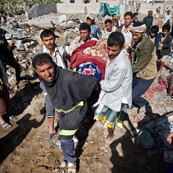 People carry the body of a woman covered with a blanket from under the rubble of houses destroyed by Saudi airstrikes near Sanaa Airport, Yemen, Thursday.