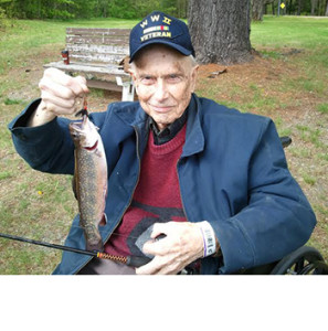 Ezra Smith holds up a brook trout he caught in the Togus pond on May 24, 2015.