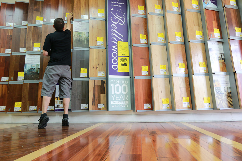 Kiel Skrobacz, an assistant store manager at Lumber Liquidators in Lutz, Fla., sticks yellow sale tags on flooring products recently. The founder and chairman of the company has said that the retailer currently has no plans to stop selling laminate flooring made in China. The Associated Press