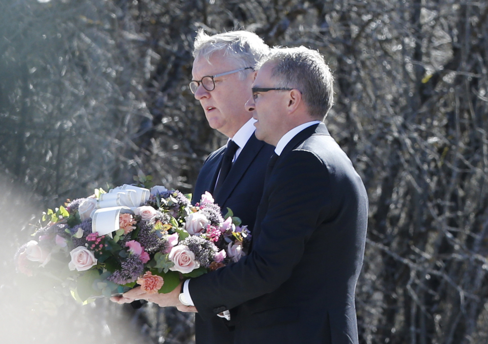 CEOs of Germanwings Thomas Winkelmann, and Lufthansa Carsten Spohr, right,  flowers to a  memorial stone  erected as a monument, set up in memory of the victims  of the Germanwings jet crash, in Le Vernet, France, Wednesday.