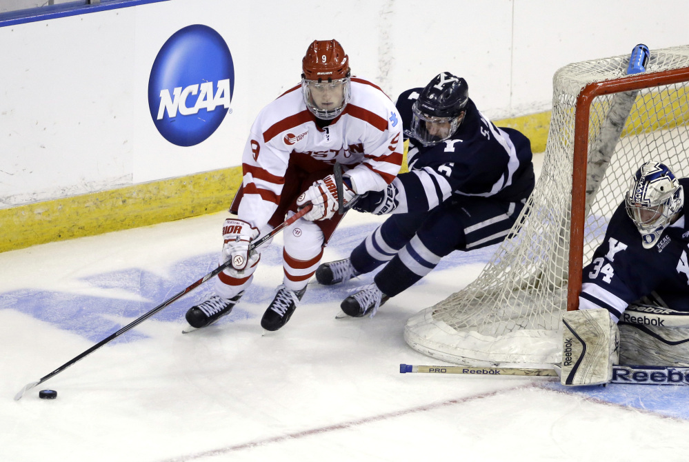 Boston University's Jack Eichel, front, handles the puck against Yale's Stu Wilson as goaltender Alex Lyon (34) protects the net in the third period of a regional semifinal game last Friday in Manchester, N.H. Eichel, a freshman, led the nation in scoring this season.