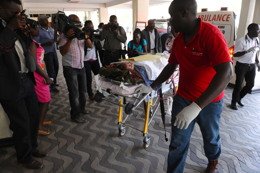Medics help an injured person airlifted to Kenyatta National Hospital in Nairobi, Kenya, on Thursday after an attack at Garissa University College in northeastern Kenya.