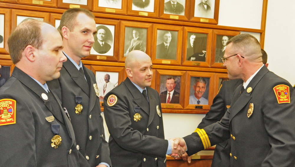 Augusta Fire Lt. Art True, left, and firefighter/paramedics Dan Freeman and Rich Beaudoin received Medals of Valor from Battalion Chief John Bennett for rescuing residents of an apartment complex fire in Gardiner during an Augusta City Council meeting on Thursday in Augusta City Center.
