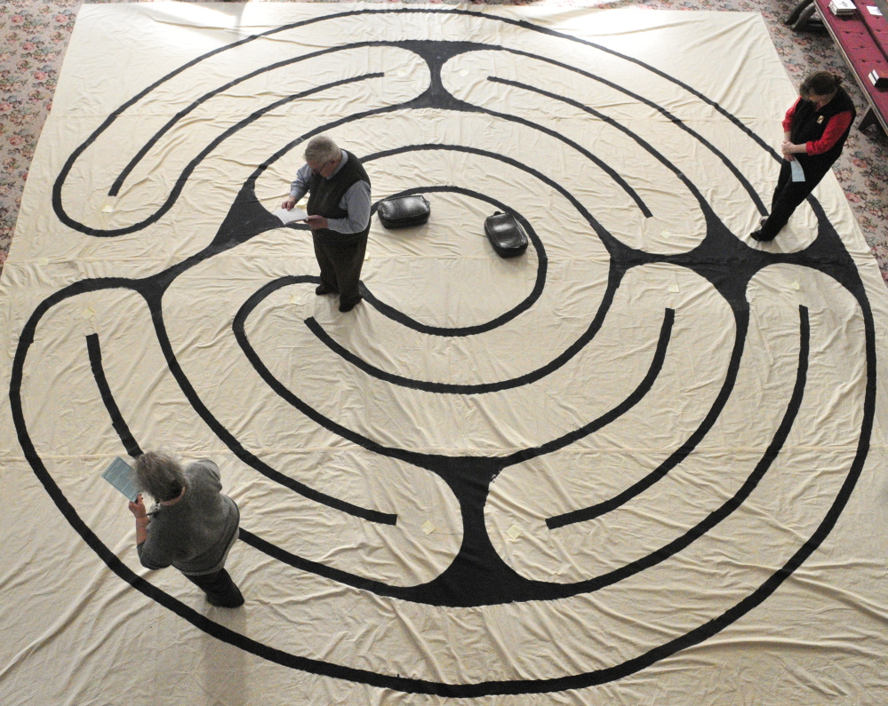 Suzan Katzir, left, the Rev. Jim Gill and Jenifer Lewis walk the labyrinth on Friday in the Winthrop Center Friends Meeting House where the St. Andrew's Episcopal Church meets.