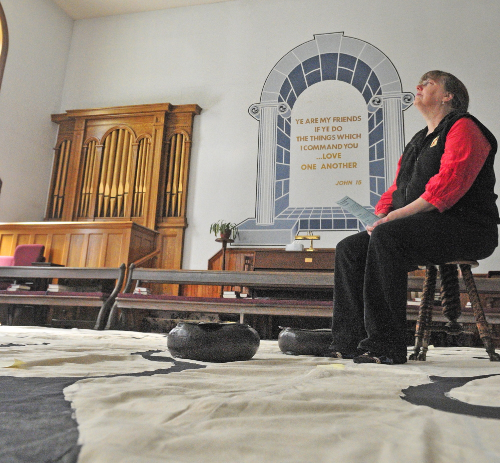 Jenifer Lewis sits on a stool meditating at the center of the labyrinth on Friday in the Winthrop Center Friends Meeting House where the St. Andrew's Episcopal Church meets.