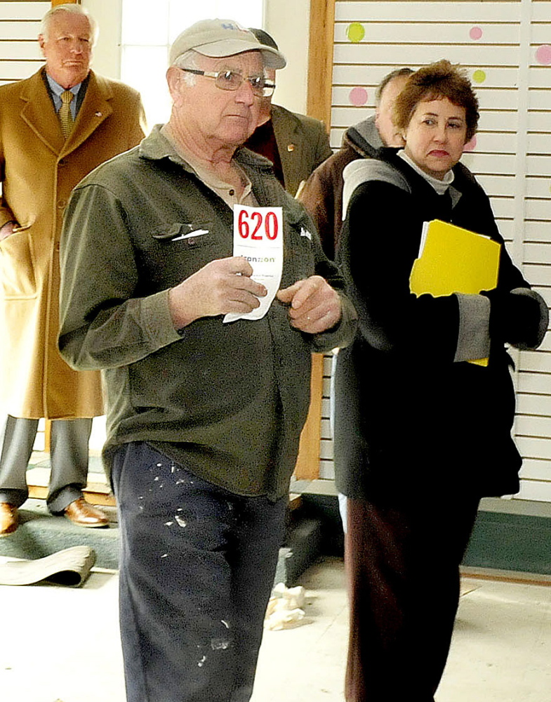 Earl Farris holds up his bidding card after making the winning bid on the former A.L. Weeks & Son business auctioned off in Waterville on Thursday.