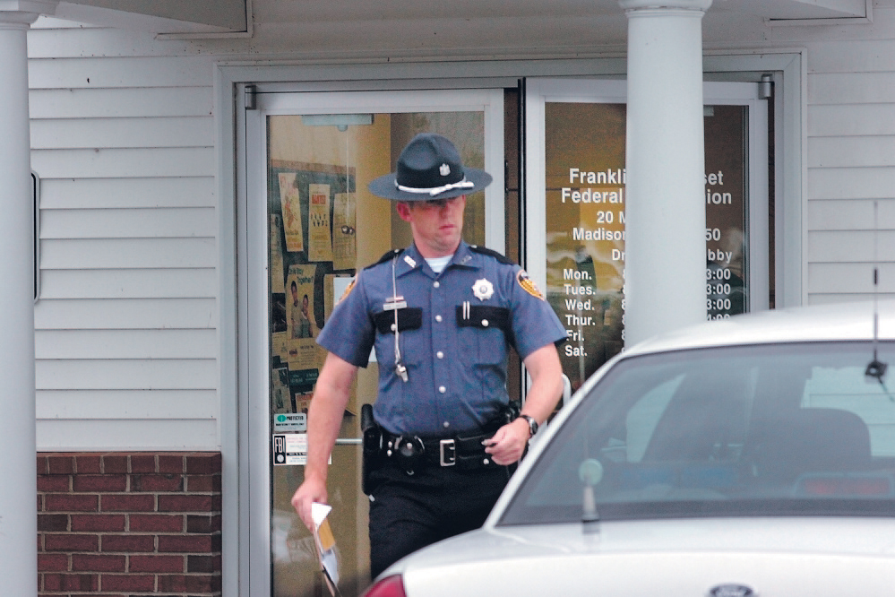 Madison police officer Kevin Hartley returns to his cruiser while investigating an armed robbery at the Franklin Somerset Federal Credit Union in Madison in 2009. Town residents will weigh in on whether to eliminate the town's police department in June and instead contract with the Somerset County Sheriff's Department. Staff file photo by David Leaming
