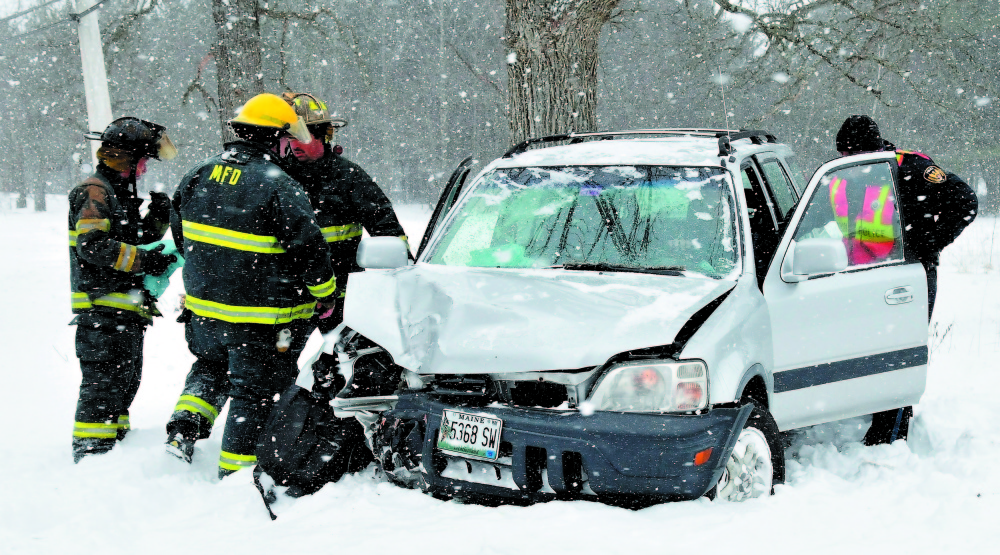 Madison police officer Brett Lowell, right, assists at a car accident in the town in February 2013. Town residents will vote in June on whether to eliminate the town's police department and instead contract with the Somerset County Sheriff's Department.