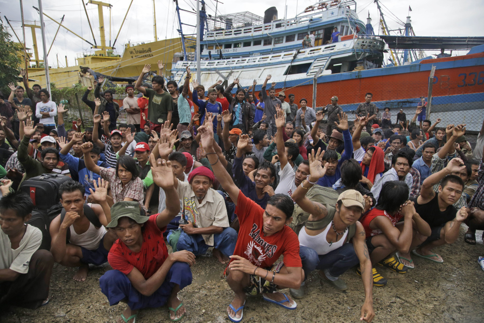 Burmese fishermen at the Aru Islands, Indonesia compound raise their hands as they are asked who among them want to go home.