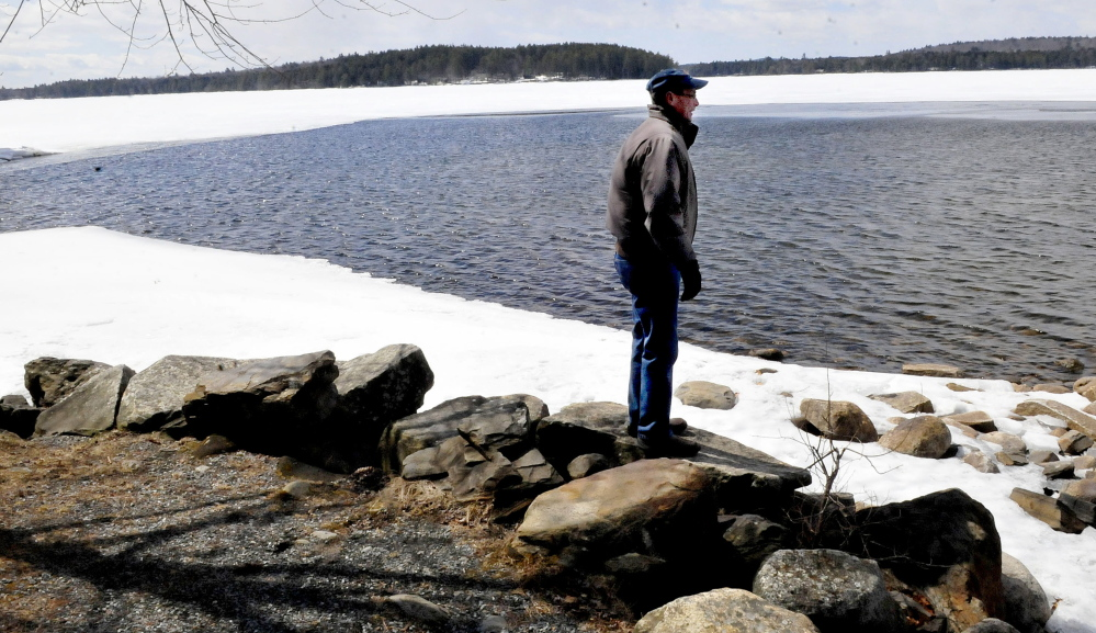 Tim Comeford looks out on Long Pond in Belgrade as ice continues to recede on Sunday. Comeford said the ice usually goes out the third week of April.