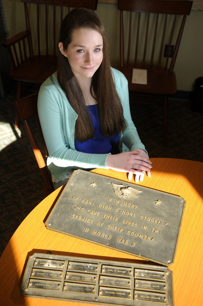 Cony High School senior Kelsey Rohman with a plaque remembering graduates lost in World War II at the Augusta school last week.  Rohman is attempting to have memorials from the old school displayed again at the new school.