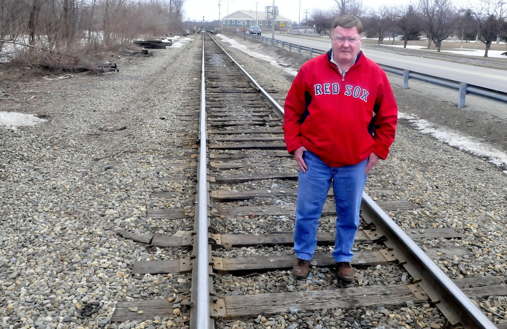 Waterville City Council Chairman Fred Stubbert stands on railroad track where the passenger railroad station used to be in Waterville along Colby Street on Thursday. The City Council will discuss a resolution to restore passenger service.