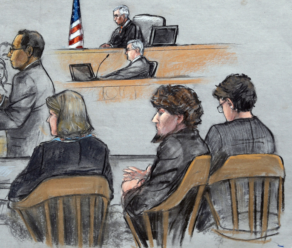 In this courtroom sketch, Assistant U.S. Attorney Aloke Chakravarty, left, is depicted addressing the jury as defendant Dzhokhar Tsarnaev, second from right, sits between his defense attorneys during closing arguments in Tsarnaev's federal death penalty trial Monday, in Boston.