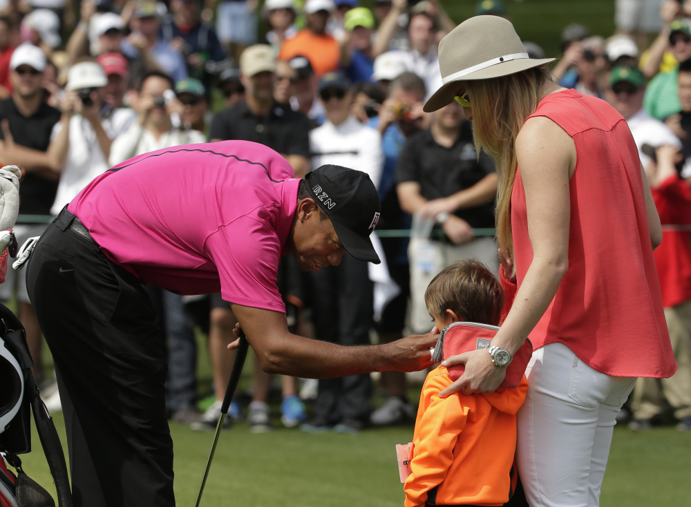 Lindsey Vonn watches as Tiger Woods speaks to his son Charlie during a practice round for the Masters golf tournament Tuesday in Augusta, Ga.