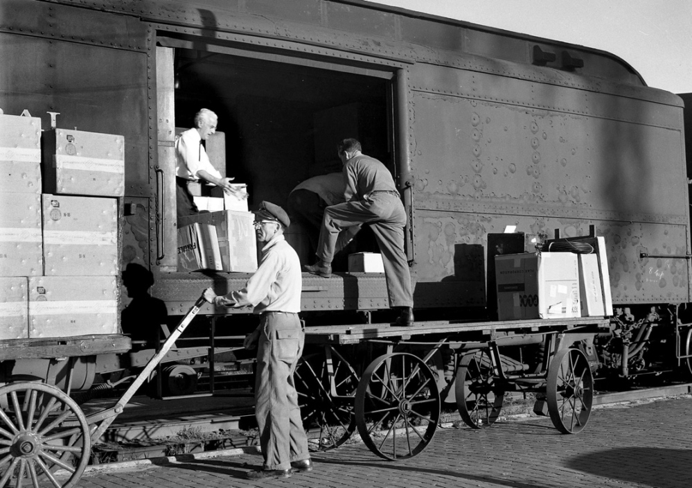 """Maine Central Railroad workers load a special """"merchandising train"""" which was launched in September 1960 to carry goods and U.S. Mail after the end of passenger train service through Waterville station."""