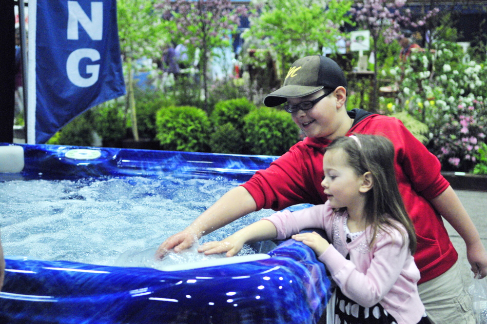 Cooper Hall, top, and Olivia Hall test the water in a hot tub during last year's Manchester Lions Home and Garden Show at Augusta Civic Center.