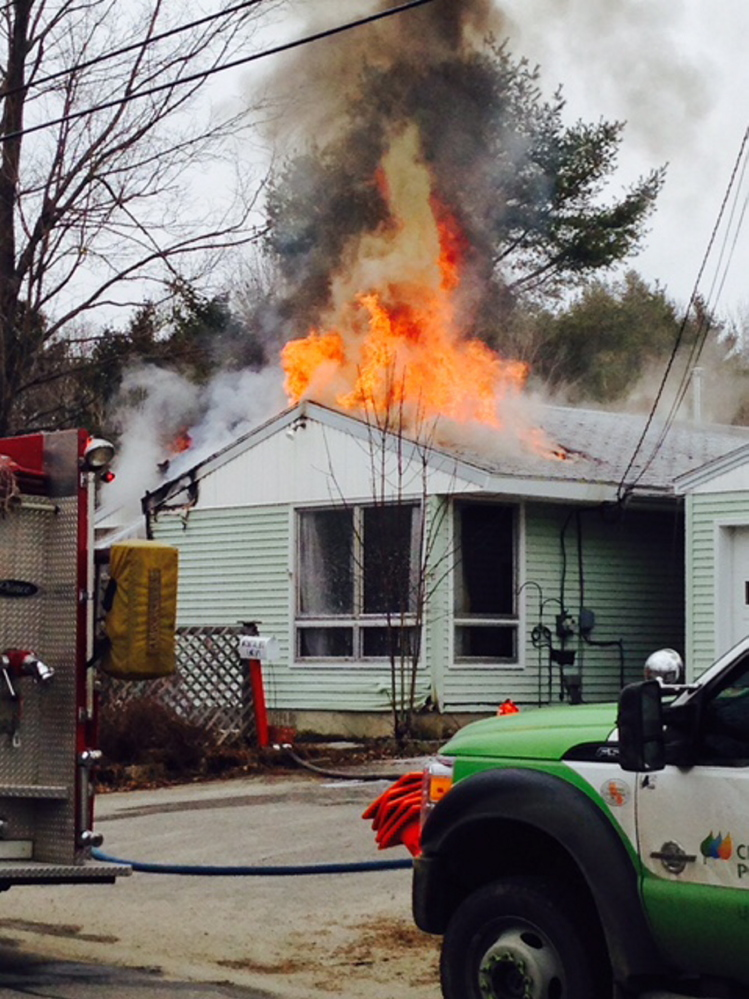 Flames shoot out the roof of a home at 81 Bowman St. in Farmingdale on Wednesday.