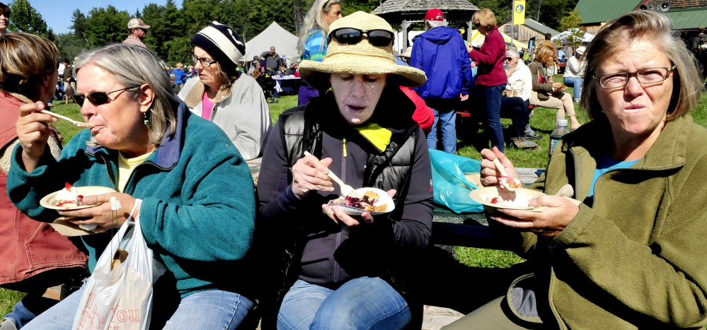 Fairgoers stop for dessert during the Maine Organic Farmers and Gardeners Association signature event, the Common Ground Country Fair, in Unity in 2014. MOFGA is among 15 organizations that have filed suit over USDA rule changes concerning the use of non-organic or synthetic substances used to produce food. Enjoying the wares, from left, are Barb Wood, Amy Howard and Myra Wilkinsen.