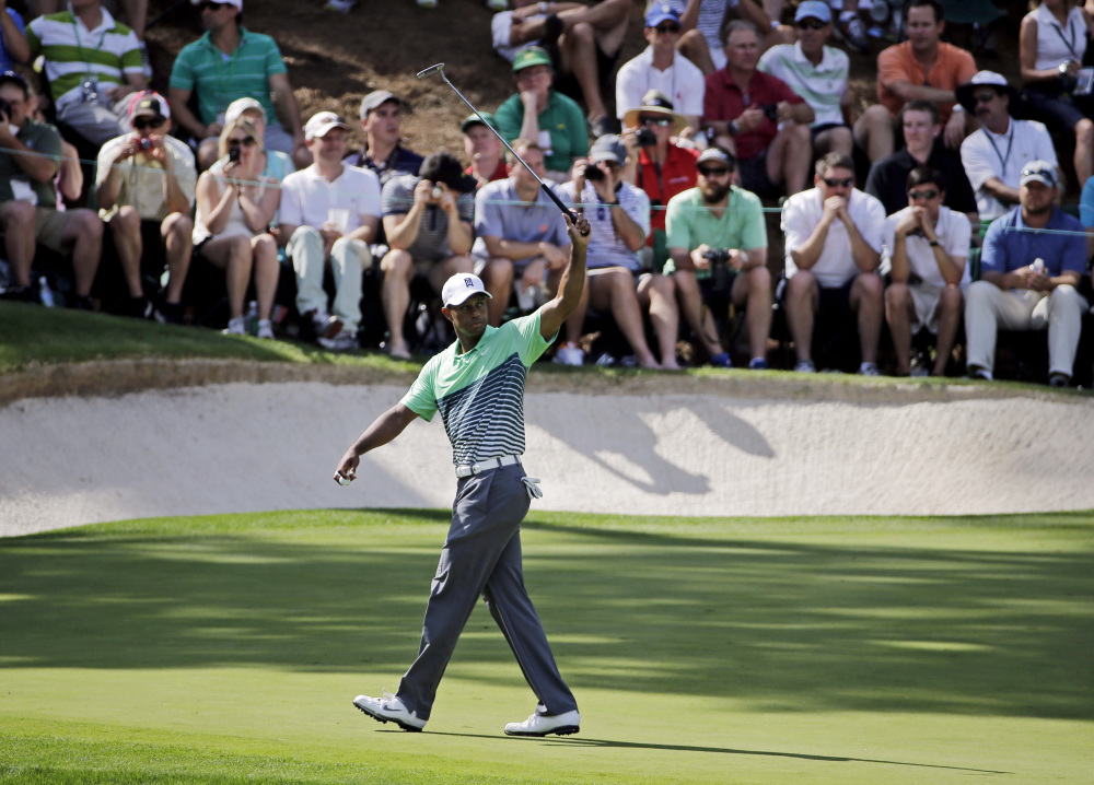 Tiger Woods waves his putter during the Par 3 contest Wednesday at the Masters in Augusta, Ga.