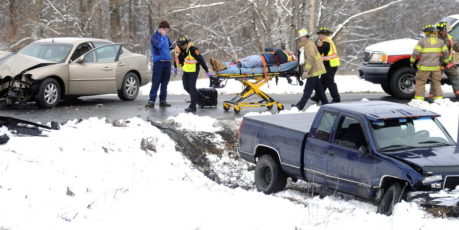 Rescue workers roll a patient to an ambulance at the intersection of Town Farm Road and Winthrop Street in Hallowell Thursday following a two-car collision.